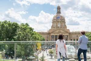 Two people look out at the Alberta Legislature building.