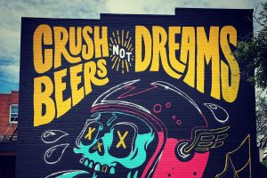 """A giant skull with """"Crush Beers Not Dreams"""" written on a wall."""