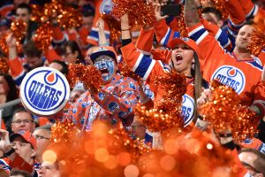 The crowd cheers at an Edmonton Oilers hockey game.