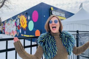 Caroline Stokes poses in front of the Grindstone Comedy Bistro. She is wearing sunglasses and a green and blue fur vest.