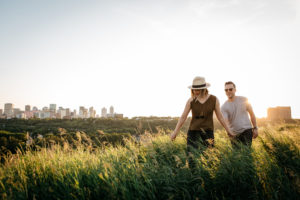 A couple walks through Edmonton's river valley with the city skyline behind them.
