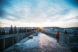 Edmonton A person walking on a bridge in the river valley at sunset