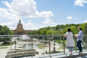 Two people view the alberta legislature from a lookout point.