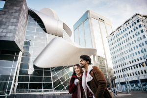A couple takes a walk in front of the Art Gallery of Alberta.