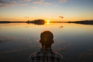 Man sitting by Astotin Lake at Elk Island National Park