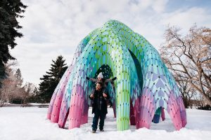 A girl sits on her dad's shoulders under a giant sculpture in Borden Park during winter.