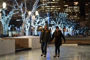 A man and a women skate at city hall, while Christmas lights shine in the background.
