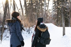 Two women walk in the snow-covered river valley during winter.