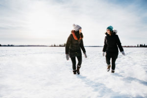 Two girls smile as they walk in the snow.