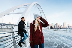 A couple looks out at the city in winter from the Walterdale Bridge.