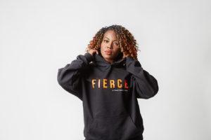 "A woman in a black hoodie that says ""Fierce"" designed by Kyn Apparel"