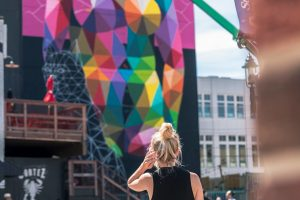 A woman looks at the Crawford Block Mural by Okuda.