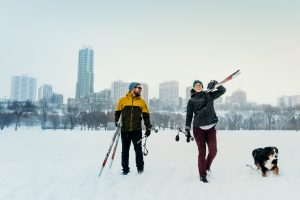 A couple cross country ski with their dog. The downtown skyline is in the background.
