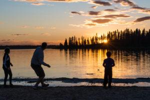 A family throws rocks at Astotin Lake.