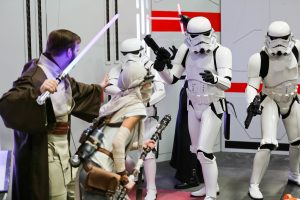 People dressed as Stormtroopers and Jedis pretend to battle at The Edmonton Comic & Entertaiment Expo.