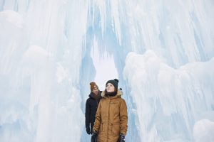 Two people walking through the archway made of ice at the Ice castles.