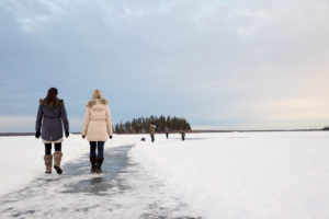 Two people walk on the frozen ice of Astotin Lake in winter.