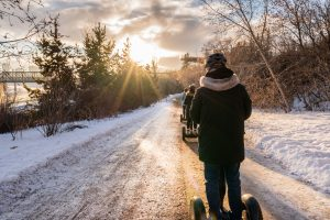 A group of people ride segways through the river valley in winter.
