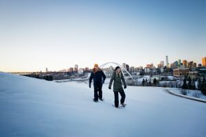 A couple snowshoe in winter with the Walterdale Bridge in the background.