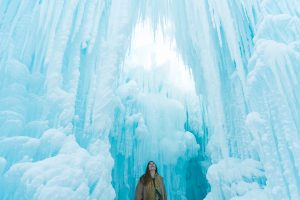 A woman looks up and admires the Ice Castles from inside the attraction.