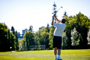 A man swings a golf club in Edmonton.