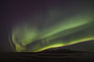 The northern lights shining green in the night sky.