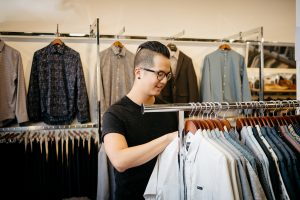 A man looks through a rack of shirts at Jaisel clothing store.