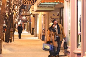 Couple walk outside on a snowy winter night, browsing the trendy shops of Whyte Avenue.