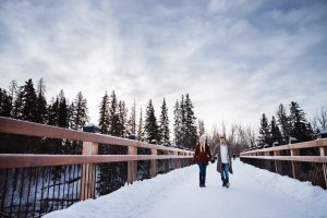 A couple walking over a bridge in the winter.