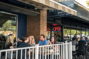 Five friends laugh on MEAT's patio in summer.