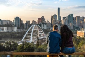 A couple looks out at the Edmonton skyline.