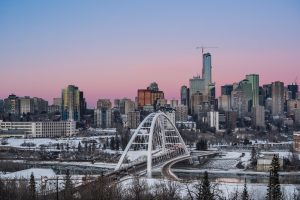 The Edmonton Skyline with a sunset in the background that makes the sky look pink.