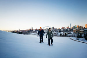 A couple snowshoeing in Edmonton with the Walterdale Bridge in the background.