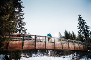 Couple stand on a bridge in Edmonton's river valley in the winter
