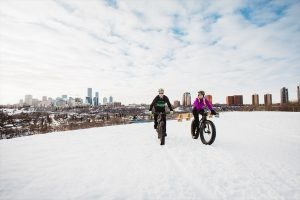 man and woman fat bike on a hill over looking Edmonton's downtown skyline