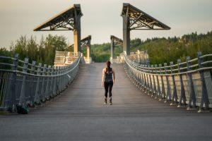 A woman walking across the Terwillegar Park Footbridge.