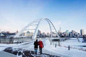 A couple walking up to the Walterdale Bridge in winter.