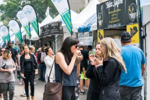 Three girls happily eat their food at Taste of Edmonton