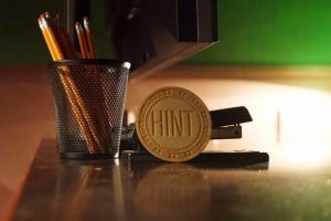 escape room, pencils and stapler on table as well as a hint token