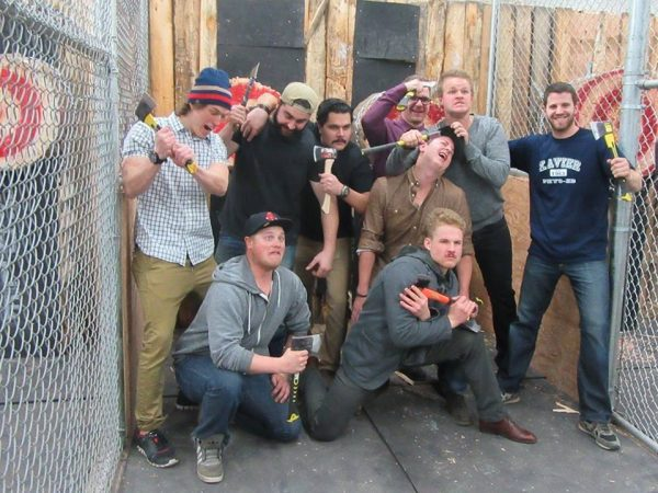 Group of men holding throwing axes at Axehole.