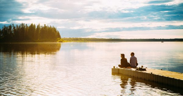 cropped two people sitting on the edge of a dock on Astotin Lake at Elk Island National Park