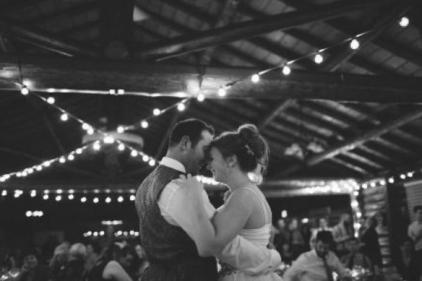The bride and groom dance under string lights