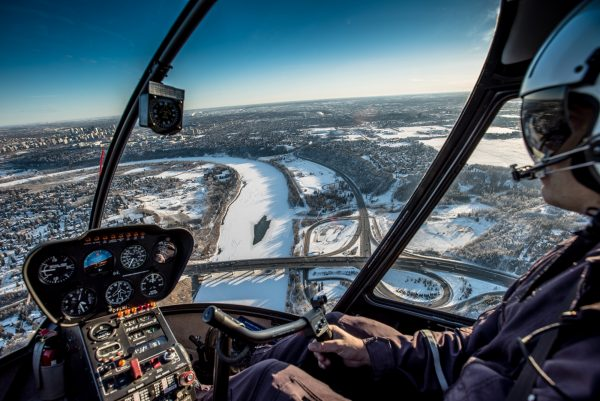 Pilot flying above city on an Edmonton regional helicopter tour