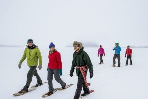 a large group of people snowshoeing at elk island national park