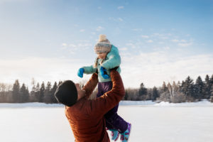 A dad holds up his daughter as they skate in Hawrelak Park.