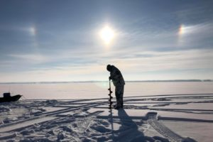 A man drills a hole in the ice in preparation to fish.