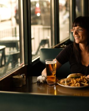 Woman enjoying burger and a beer at The Next Act Pub.