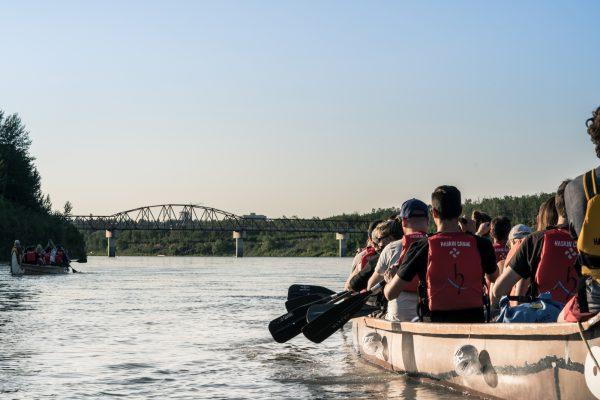 People canoe in voyager canoe along the North Saskatchewan River in Edmonton