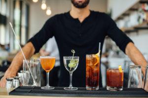 Bartender presenting drinks at District Cafe in Edmonton.