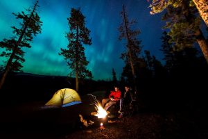 two people sitting beside a fire at night. The sky is illuminated by the Aurora Borealis